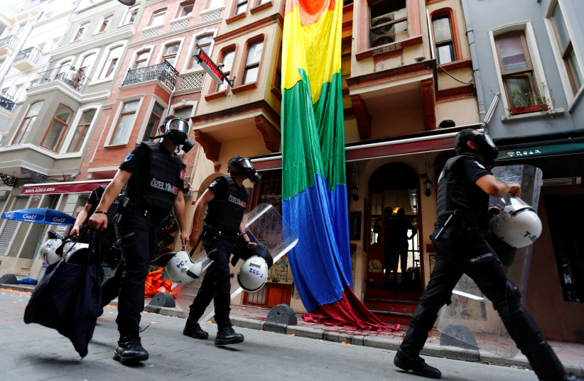 Riot police, with a rainbow flag in the background, chase LGBT rights activists as they try to gather for a pride parade in Istanbul, Turkey (photo credit: MURAD SEZER/REUTERS)