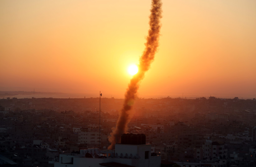 A trail of smoke can be seen as rockets are fired from Gaza towards Israel (photo credit: REUTERS/MOHAMMED SALEM)