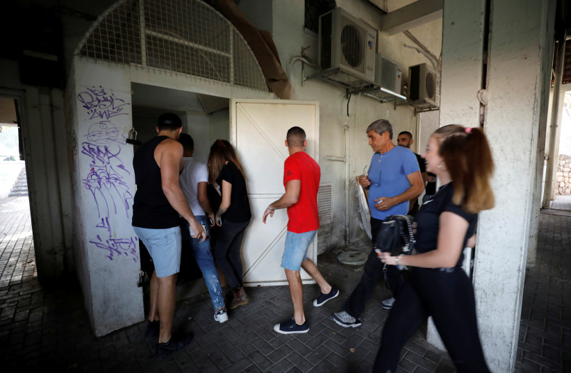 People run to take shelter as a siren warning of incoming rockets sound as a spike in cross-border violence with Gaza continues, in Ashkelon, southern Israel (photo credit: AMIR COHEN/REUTERS)