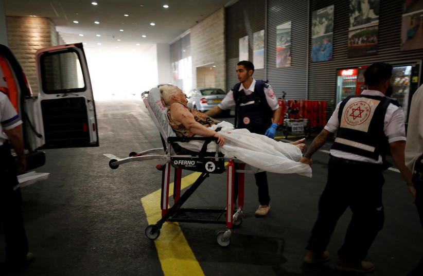 An injured woman is evacuated to hospital after a rocket was fired from Gaza into Israel, in Ashkelon, southern Israel (photo credit: REUTERS/AMIR COHEN)
