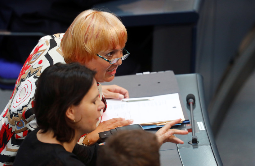 Katrin Goering-Eckardt and Claudia Roth from the Greens party react during the 2018 budget debate at the lower house of parliament Bundestag in Berlin, Germany, May 16, 2018 (photo credit: REUTERS/HANNIBAL HANSCHKE)