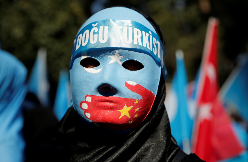 An ethnic Uighur demonstrator wears a mask as she attends a protest against China in front of the Chinese Consulate in Istanbul (photo credit: HUSEYIN ALDEMIR/REUTERS)