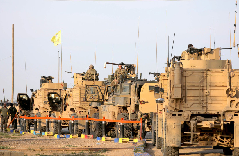 AMERICAN SOLDIERS stand near military trucks at al-Omar oil field in Deir Al Zor, Syria, on March 23.  (photo credit: REUTERS)