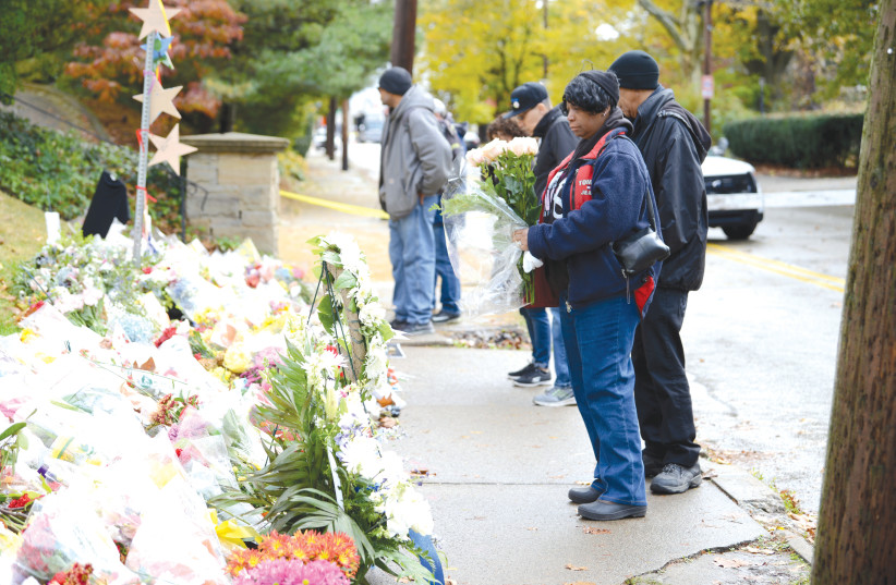 People gather at makeshift memorial a block from the scene the shooting last year of the Tree of Life Synagogue in Pittsburgh Pennsylvania.   (photo credit: ALAN FREED/REUTERS)