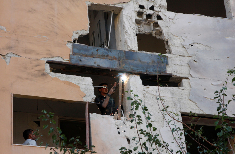 A worker fixes the damage to a building from an Israeli attack in Damascus, Syria November 20, 2019. (photo credit: REUTERS/OMAR SANADIKI)