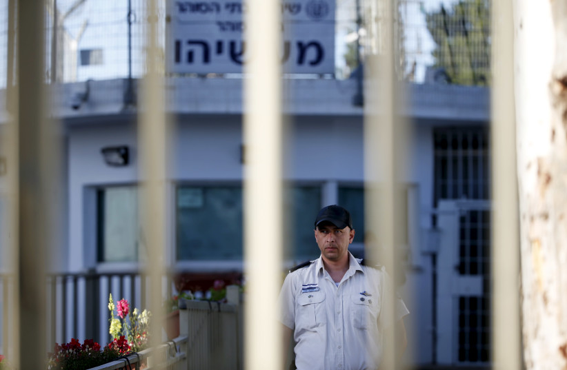 An Israeli prison guard is seen through a gate at Maasiyahu prison near Ramle, south of Tel Aviv, Israel February 15, 2016. Former Israeli Prime Minister Olmert begins his 19-month prison sentence at Maasiyahu prison on Monday, making him the first former head of government in Israel to go to prison (photo credit: BAZ RATNER/REUTERS)