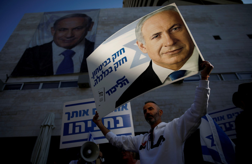 "Supporters of Israeli Prime Minister Benjamin Netanyahu protest outside Likud Party headquarters in Tel Aviv, Israel November 22, 2019. The placards in Hebrew read, ""Strong in security, strong in Economy "" (photo credit: CORINNA KERN/REUTERS)"