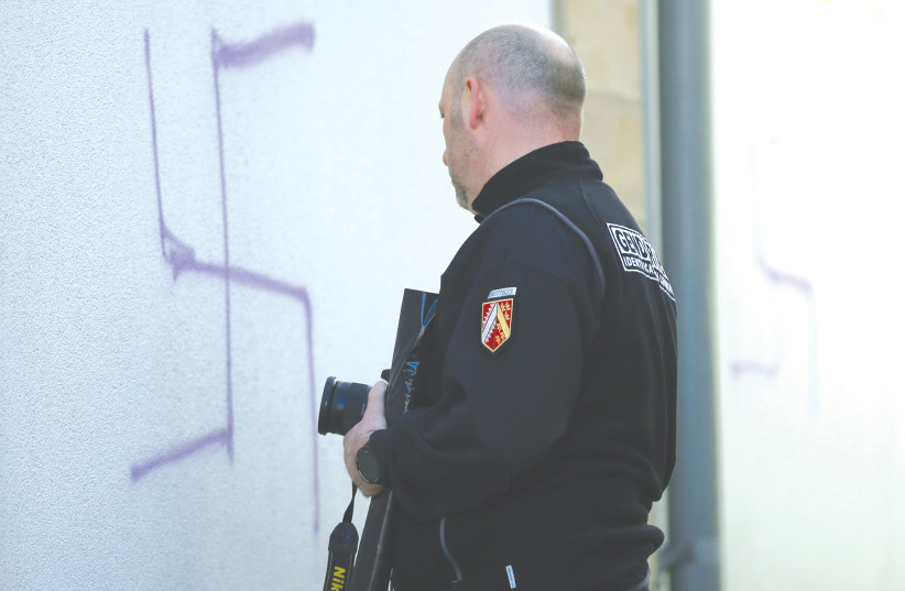 A FRENCH gendarme inspects swastikas painted on a wall of a former synagogue turned into a cultural center in Mommenheim near Strasbourg. (photo credit: REUTERS)
