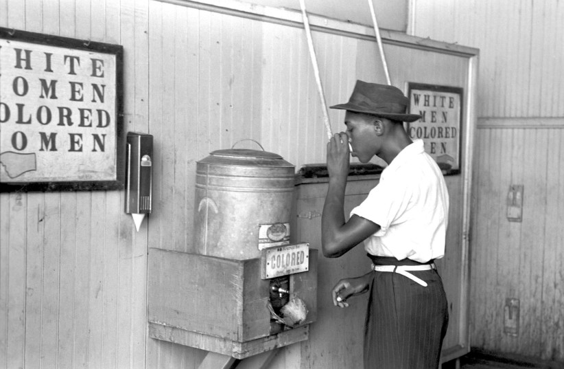 AN AFRICAN AMERICAN uses a 'colored' water fountain in Segregation-era American South. (photo credit: PIXABAY)