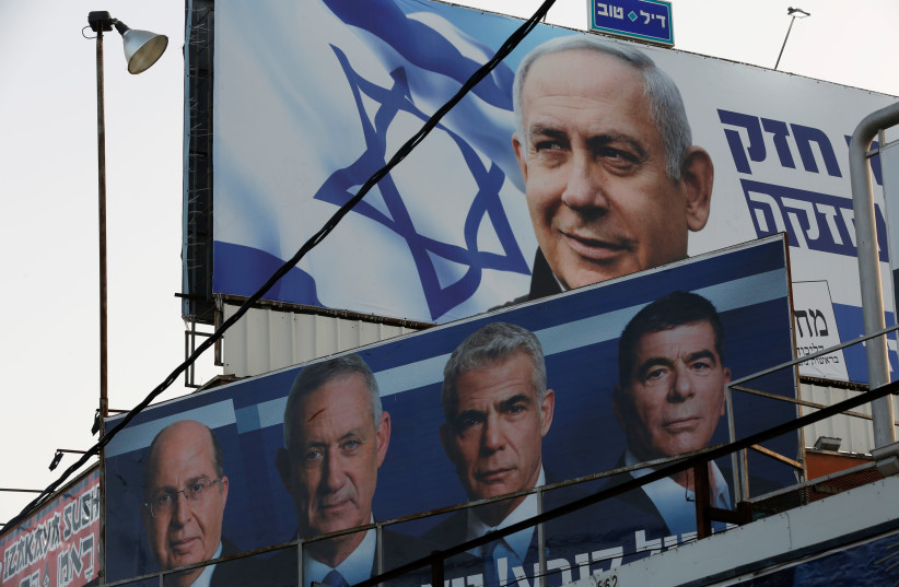 A Likud party election campaign billboard depicting Israeli Prime Minister Benjamin Netanyahu is seen above a billboard depicting Benny Gantz, leader of Blue and White party, in Petah Tikva, Israel (photo credit: NIR ELIAS / REUTERS)