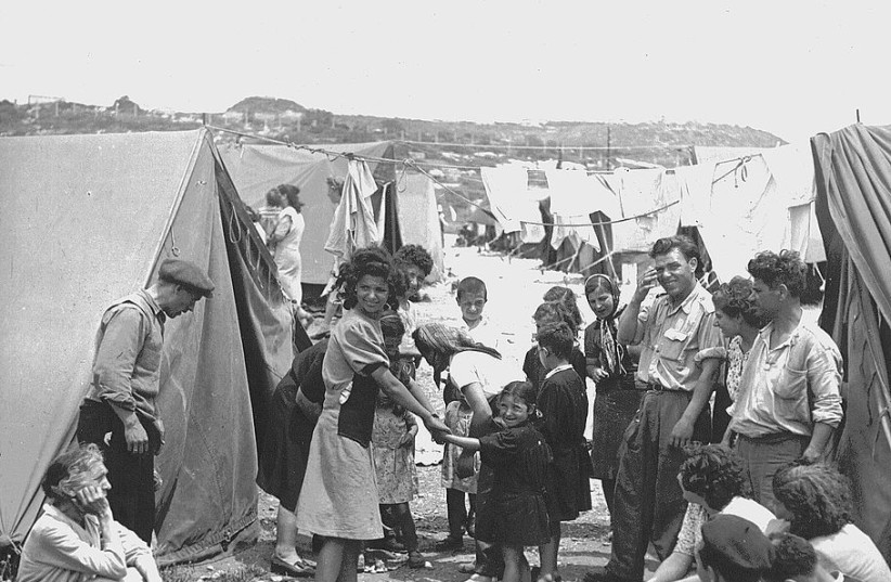 Iraqi Jewish refugees stand in a refugee absorption camp. established in Israel in 1950. (photo credit: Wikimedia Commons)