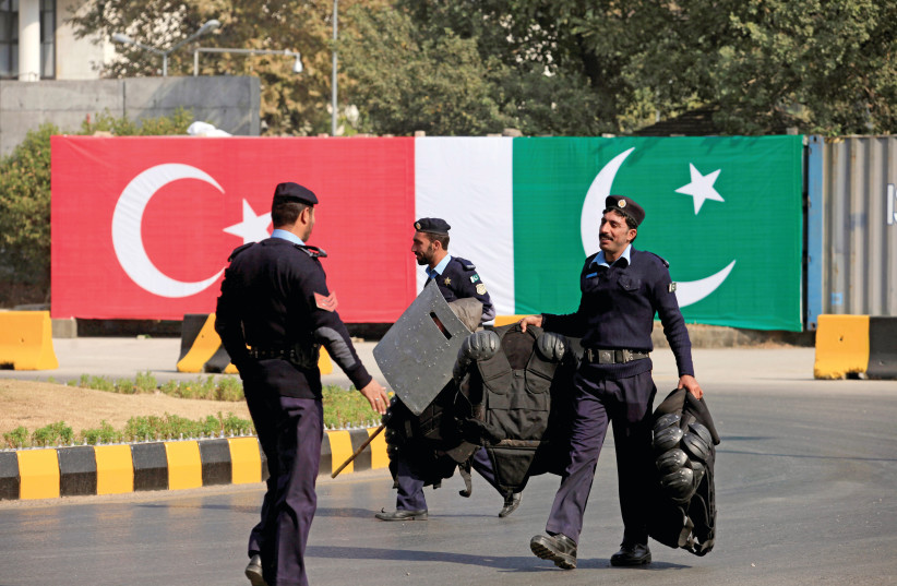 POLICEMEN WALK near the national flags of Pakistan and Turkey displayed along a road ahead of a visit of Turkish President Recep Tayyip Erdogan in Islamabad in 2016.  (photo credit: FAISAL MAHMOOD/REUTERS)