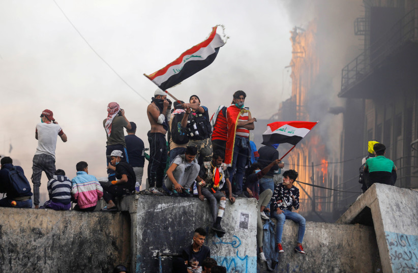 An Iraqi demonstrator carries the Iraqi flag during ongoing anti-government protests, in Baghdad, Iraq (photo credit: REUTERS/KHALID AL MOUSILY)
