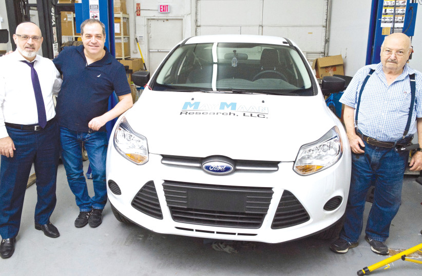 YEHUDA SHMUELI and his sons, Eitan and Doron with the car prototype  (photo credit: DANIEL GODOY)