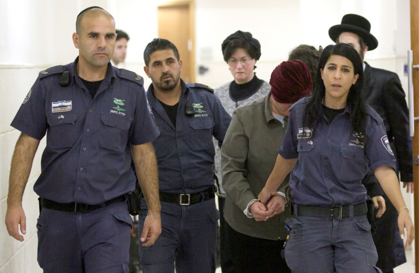 MALKA LEIFER, surrounded by Israel Prison Service guards, covers her face in Jerusalem District Court on February 14, 2018.  (photo credit: AVSHALOM SHOSHANI)