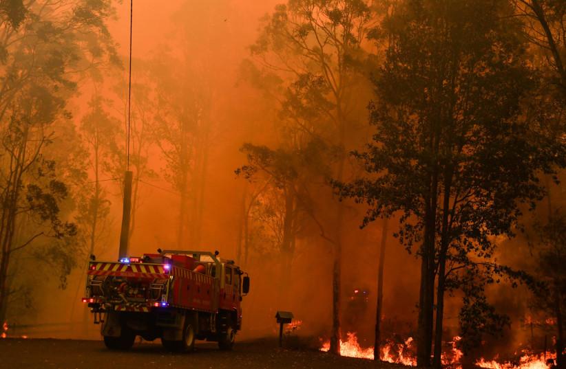Fire trucks are seen during a bushfire in Werombi, 50 km southwest of Sydney, Australia. (photo credit: AAP IMAGE/MICK TSIKAS/VIA REUTERS)