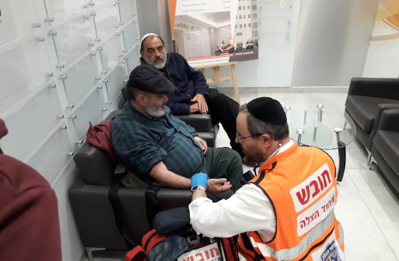 David Ben Avraham is treated by a paramedic following his release from jail, while friend Haim Pereg sits by.  (photo credit: COURTESY UNITED HATZALAH)