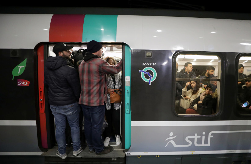 Passengers stand in the door of a packed metro train at the Gare du Nord RER station in Paris (photo credit: REUTERS/ERIC GAILLARD)