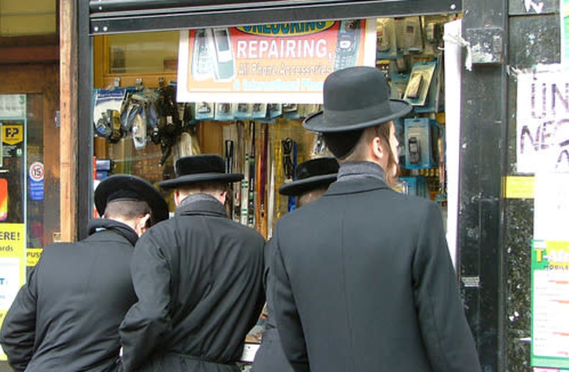 Ultra-Orthodox Jews stand in a street in the predominantly Jewish neighborhood of Stamford Hill in the UK (photo credit: Wikimedia Commons)