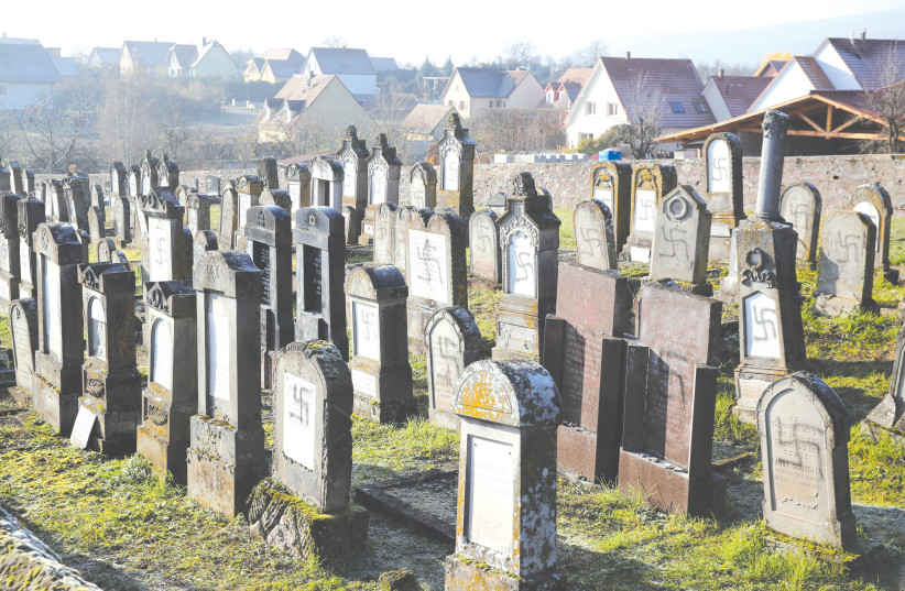 GRAVES DESECRATED with swastikas are seen at the Jewish cemetery in Westhoffen, near Strasbourg, France. (photo credit: REUTERS)