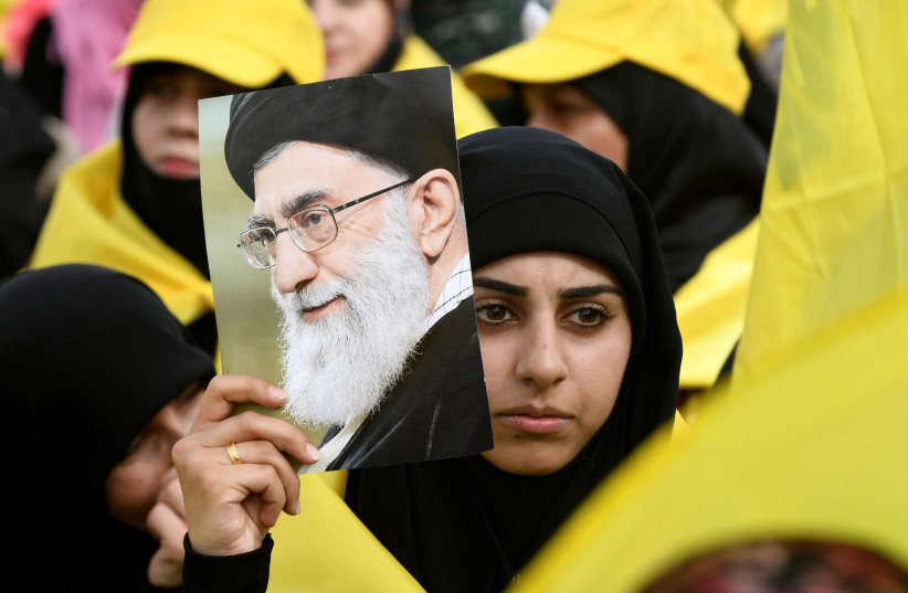 A woman carries a picture of Iran's Supreme Leader Ayatollah Ali Khamenei as she watches Lebanon's Hezbollah leader Sayyed Hassan Nasrallah appear on a screen during a live broadcast to speak to his supporters at an event marking Resistance and Liberation Day in the Bekaa Valley, Lebanon, May 25, 20 (photo credit: HASSAN ABDALLAH / REUTERS)