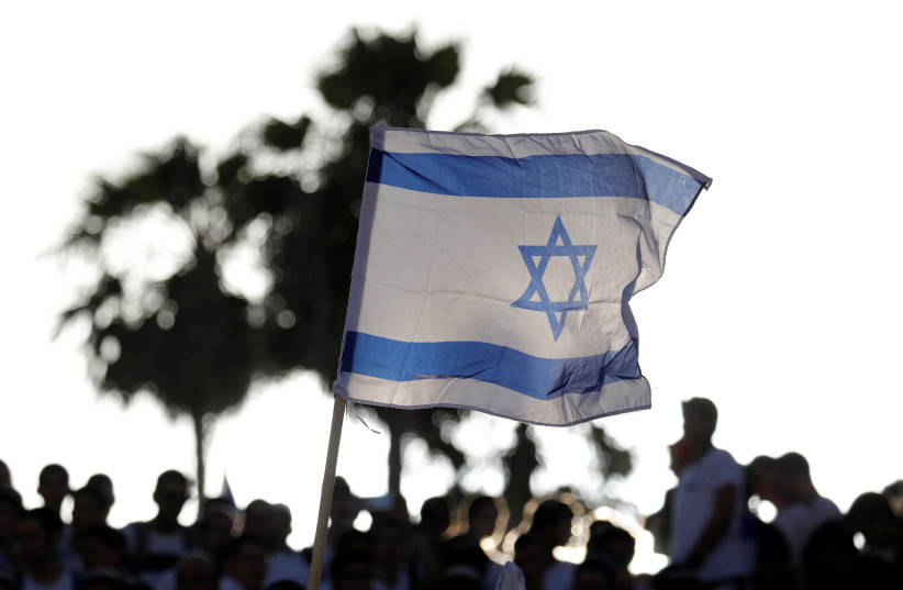 """Jewish youth wave Israeli flags as they participate in a march marking """"Jerusalem Day"""", near Damascus Gate in Jerusalem's Old City June 2, 2019 (photo credit: AMIR COHEN/REUTERS)"""