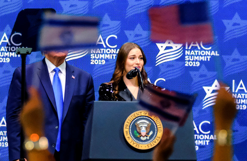 US President Donald Trump stands next to a former student of New York University speaking at the Israeli-American Council Summit in Hollywood, Florida, U.S. December 7, 2019 (photo credit: REUTERS/MARIA ALEJANDRA CARDONA)