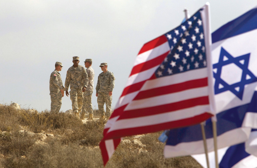 US SOLDIERS stand in the background next to Israeli and American flags during an exercise in Israel. (photo credit: REUTERS)