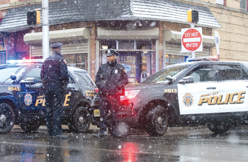JERSEY CITY police work at the scene the day after an hours-long gun battle with two men around a kosher market in Jersey City, New Jersey. (photo credit: REUTERS)