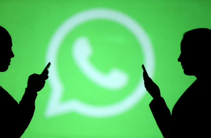 Silhouettes of mobile users are seen next to a screen projection of Whatsapp logo in this picture illustration (photo credit: REUTERS)