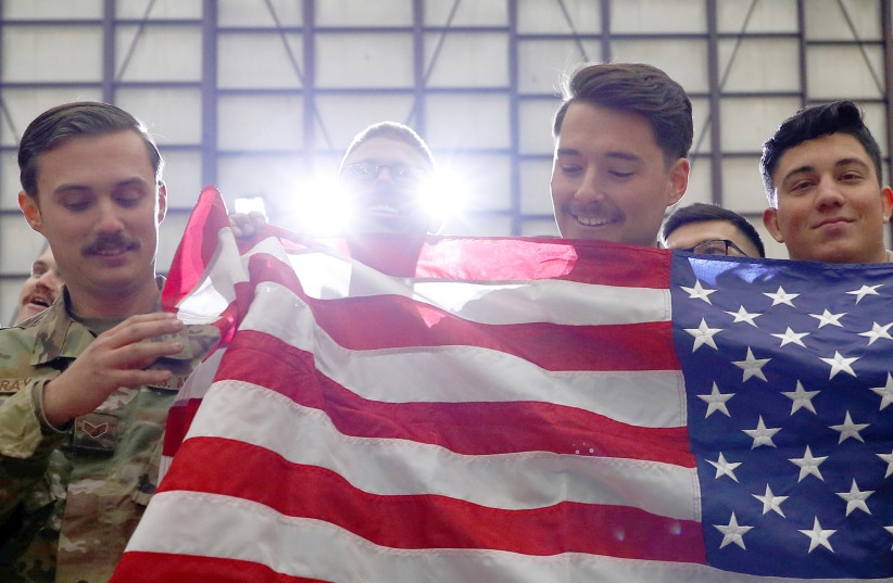 US TROOPS hold up an American flag as President Donald Trump delivers remarks to military personnel, in an unannounced visit to Bagram Air Base, Afghanistan, on November 2 (photo credit: REUTERS)
