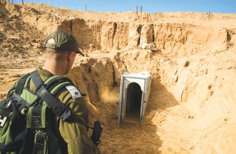AN IDF SOLDIER stands next to an entrance to a cross-border attack tunnel dug from Gaza to Israel, near Kissufim last year.  (photo credit: JACK GUEZ)