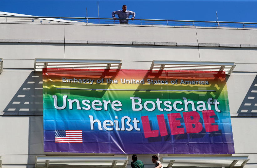 "U.S. Ambassador to Germany Richard Grenell watches as workers attach a banner, which reads ""Our message is love"", at the U.S. Embassy ahead of the Gay Pride parade, also called Christopher Street Day (CSD) parade in Berlin, Germany (photo credit: REUTERS/FABRIZIO BENSCH)"