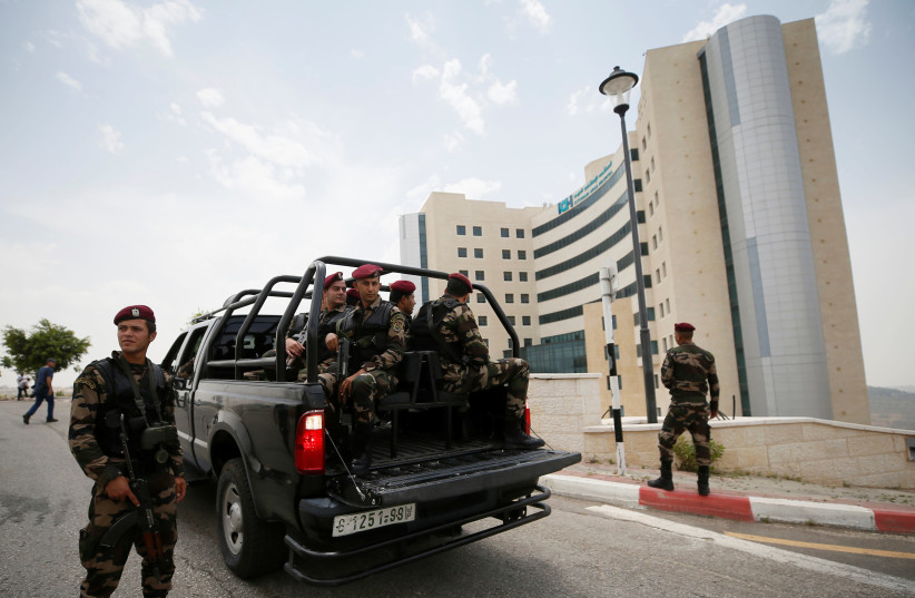 Palestinian security forces guard outside al-Istishari hospital in Ramallah (photo credit: MOHAMAD TOROKMAN/REUTERS)