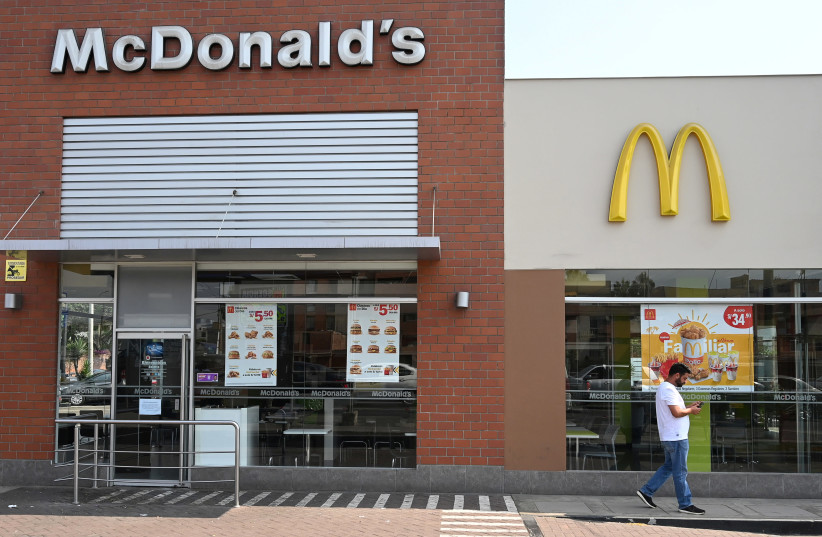 A person walks next to a closed McDonald's restaurant, one of all 29 locations that were closed following the deaths of two teenaged employees, in Lima, Peru  (photo credit: REUTERS/GUADALUPE PARDO)