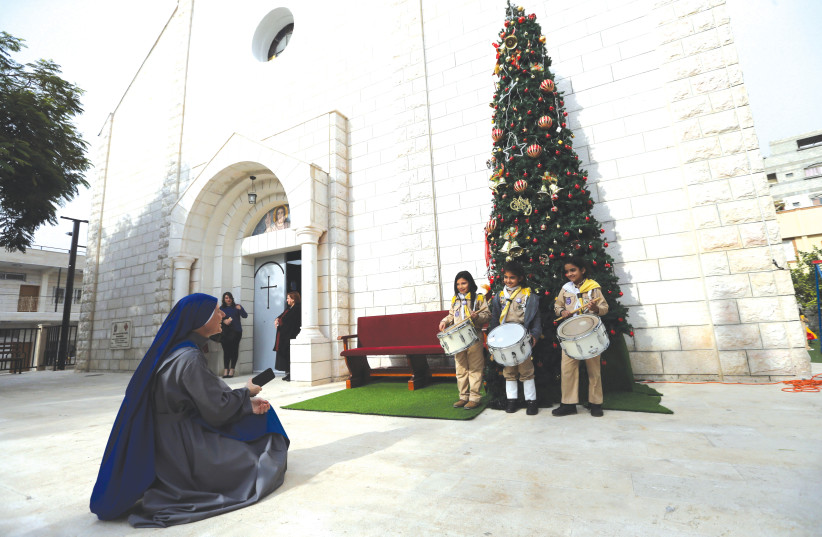 PALESTINIAN GIRL scouts pose for a photo in front of a Christmas tree outside the Holy Family Church in Gaza City.  (photo credit: REUTERS)