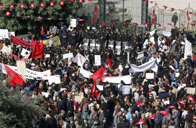 Protesters stand in front of riot police during a demonstration outside the parliamentary building in Tunis, November 2011 (photo credit: REUTERS/ZOUBEIR SOUISSI)