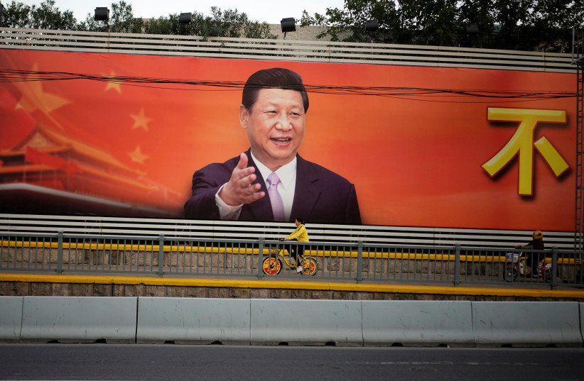 A poster with a portrait of Chinese President Xi Jinping is displayed along a street in Shanghai, China, October 24, 2017 (photo credit: ALY SONG/REUTERS)