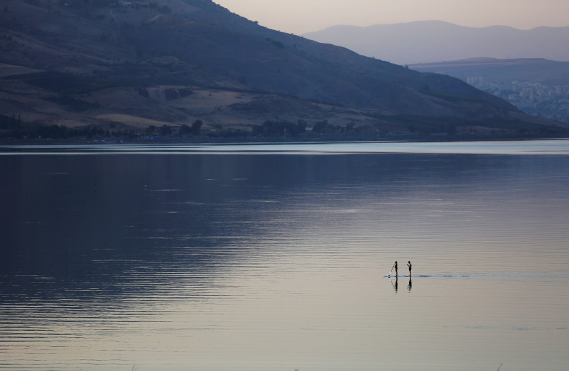 People paddle on a stand-up paddle board in the Sea of Galilee, northern Israel November 8, 2016. (photo credit: REUTERS/Ronen Zvulun)