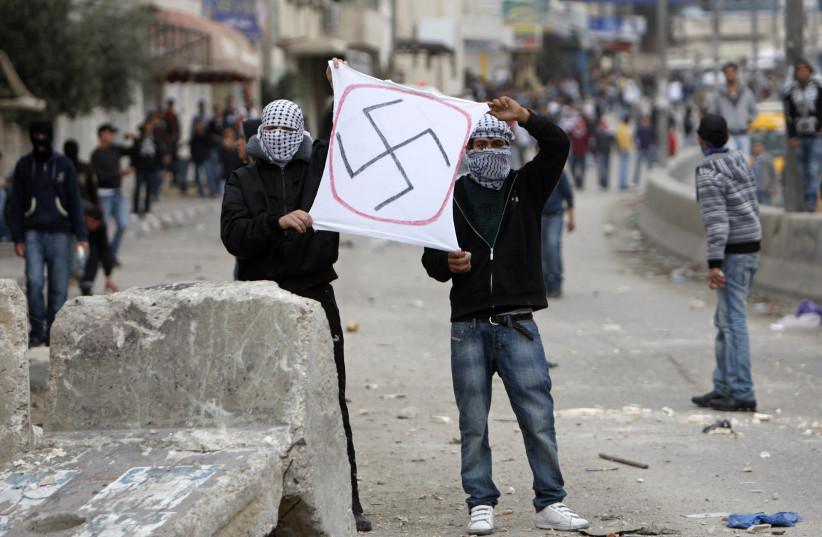 Palestinian protesters hold up a swastika in an anti-Israel protest in the West Bank. (photo credit: REUTERS)
