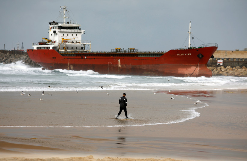 A man walks along the shore of the Mediterranean Sea as a cargo vessel that arrived at Israel's Ashdod port and was swept away when a storm began is seen nearby, close to Ashdod's port in southern Israel December 26, 2019 (photo credit: REUTERS/AMIR COHEN)