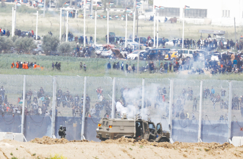 IDF Soldiers clash with Palestinians protestors at the bordr between and the Gaza Strip  (photo credit: AMIR COHEN/REUTERS)