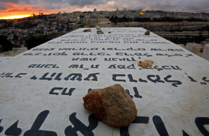 Stones placed in remembrance lie on grave tablets on the Mount of Olives Jewish cemetary as the sun sets in Jerusalem (photo credit: LASZLO BALOGH/ REUTERS)