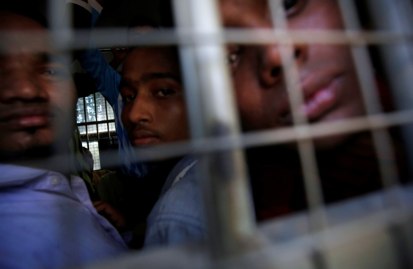 Rohingya Muslim men look out from inside a police vehicle, as they are transported from a court hearing on charges of illegally travelling without proper documents, in Pathein, Ayeyarwady, Myanmar December 20, 2019 (photo credit: ANN WANG/REUTERS)