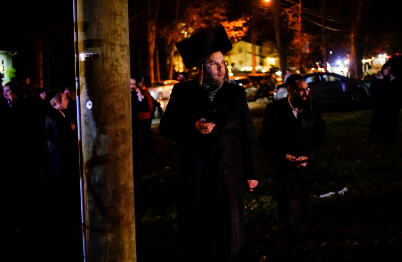 Jewish people try to take a look of the area where 5 people were stabbed at a Hasidic rabbi's home in Monsey, New York (photo credit: REUTERS)