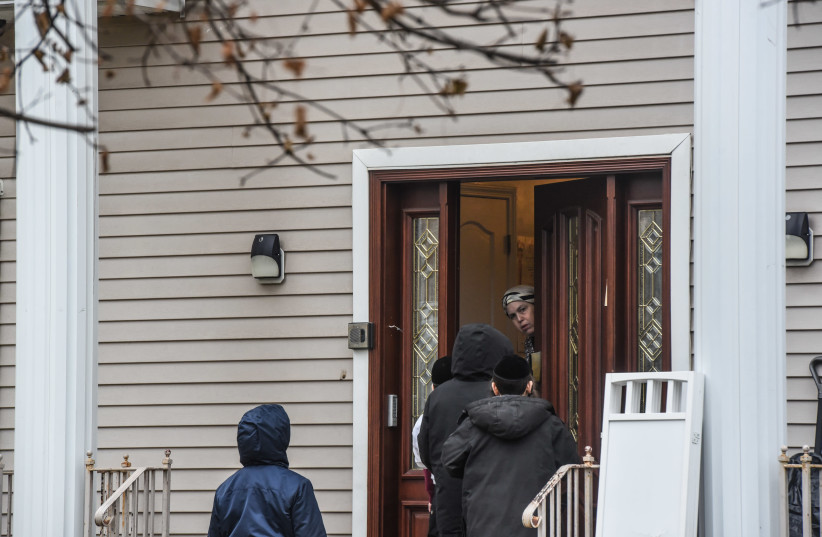 A person answers the door at the house of Rabbi Chaim Rottenberg on December 29, 2019 in Monsey, New York. Five people were injured in a knife attack during a Hanukkah party and a suspect was later arrested in Harlem. (photo credit: STEPHANIE KEITH/ GETTY IMAGES)