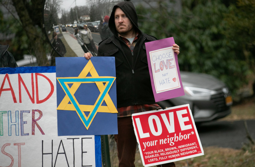 A man holds a sign outside the home of rabbi Chaim Rottenberg in Monsey (photo credit: JEENAH MOON/REUTERS)
