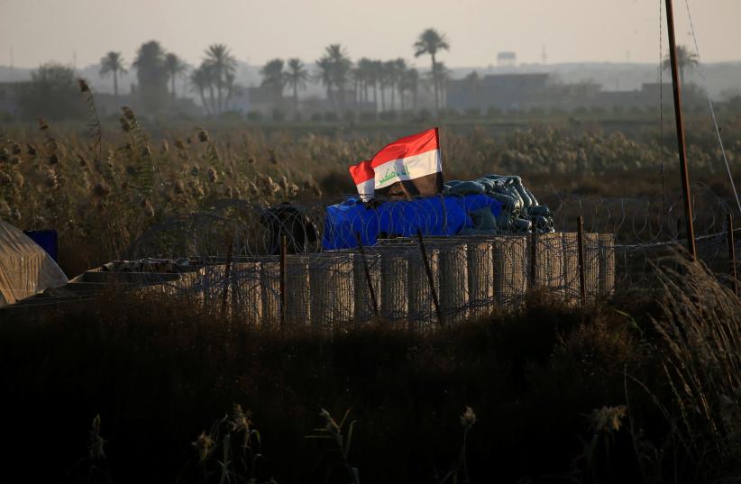 An Iraqi flag flies at a military camp near the border with Syria at al-Qaim, Iraq, November 25, 2018. (photo credit: ALAA AL-MARJANI/REUTERS)
