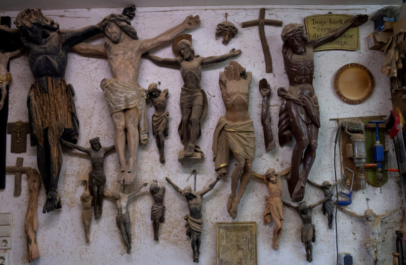 Broken statues of the crucified Jesus Christ hang on the wall in the workshop of sculptor Nikolaus Duerlich of the ethnic minority of Sorbs, in Raeckelwitz, Germany, April 5, 2019. (photo credit: REUTERS/MATTHIAS RIETSCHEL)
