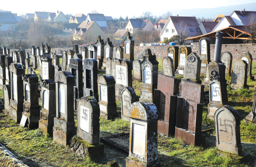 GRAVES DESECRATED with swastikas are seen at the Jewish cemetery in Westhoffen, France.  (photo credit: REUTERS)